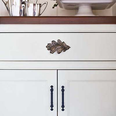 a cherry countertop and antiqued brass oak leaf and bar pulls give a custom look to the built-in hutch