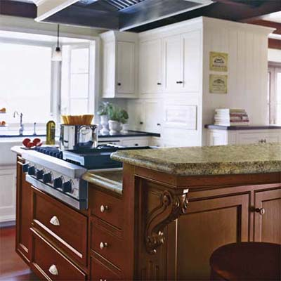 the raised snack bar on the cherry island helps hide the hardworking cooktop