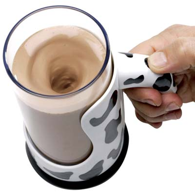 a push-button device that mixes chocolate milk in the plastic mug decorated with cow markings