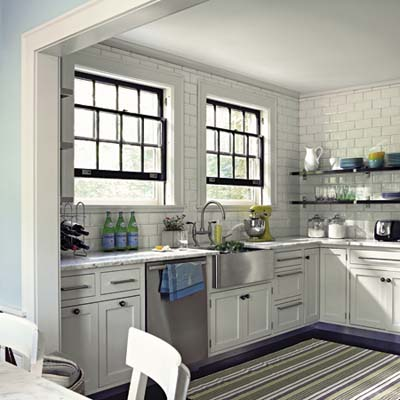 Kitchen with white subway tile, floating shelves, stainless farmhouse sink