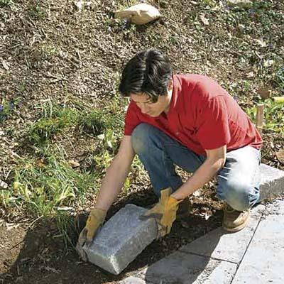 Man placing concrete block in soil