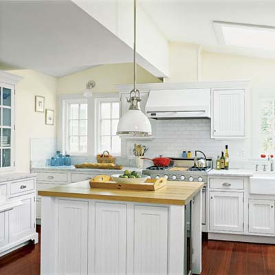 all-white kitchen with island, built in storage and vintage sytle