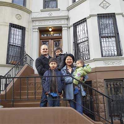 new york city house homeowners standing on the stoop outside their home