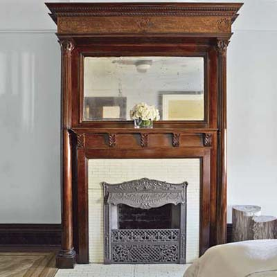 tall, built in mirror above decorative fireplace mantle in new york city house master bedroom