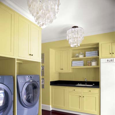 two chandeliers hanging in a yellow painted laundry room