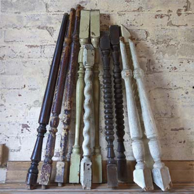 stack of salvaged wood spindles leaning against a brick wall