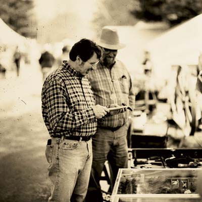 norm discusses the uses of a small vintage hammer with a dealer at the brimfield antique show in massachusetts