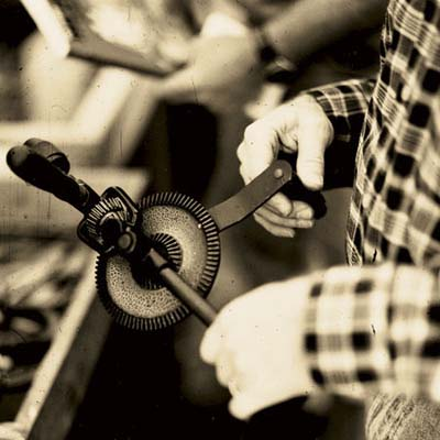 norm abram looking at a hand drill at the brimfield antique show in massachusetts