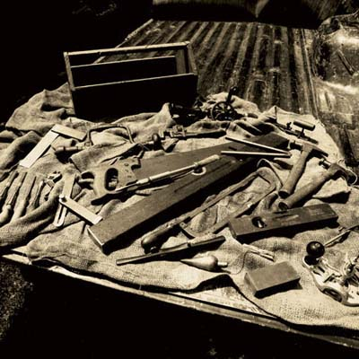 an array of antique tools, including antique hammers, chisels, hand planes, levels, compass, hand planes, and more