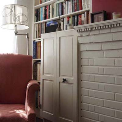 bookcases built into the space between mantel and window, with salvaged shutters as doors