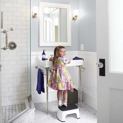 little girl in front of console sink in remodeled bathroom