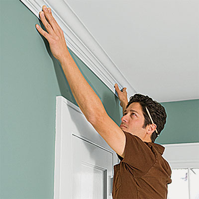 person hanging crown molding in an interior room