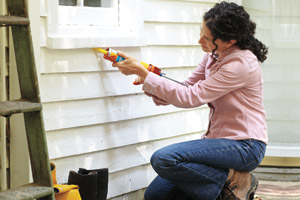 woman caulking window for energy efficiency