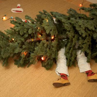Man lying on floor underneath fallen christmas tree
