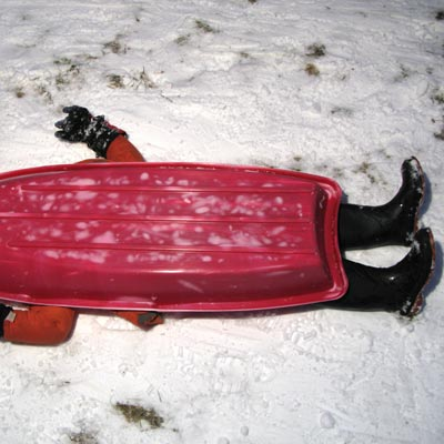 child laying under sled in snow