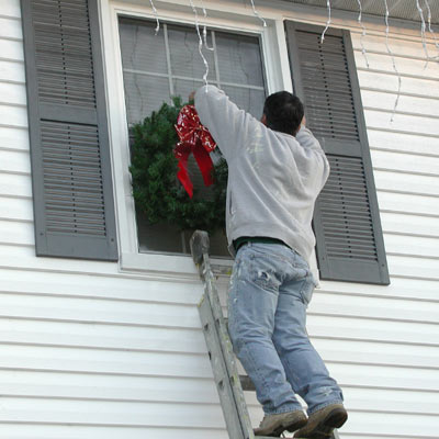 man on ladder decorating exterior of house for holidays