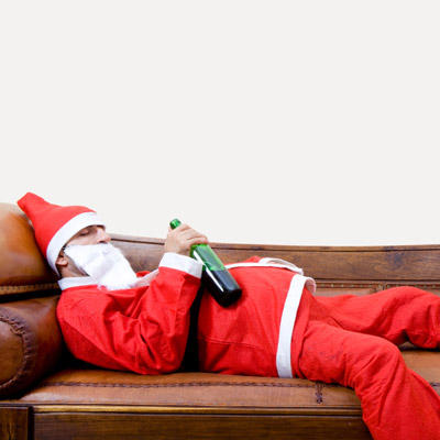 man in santa suit passed out with wine bottle