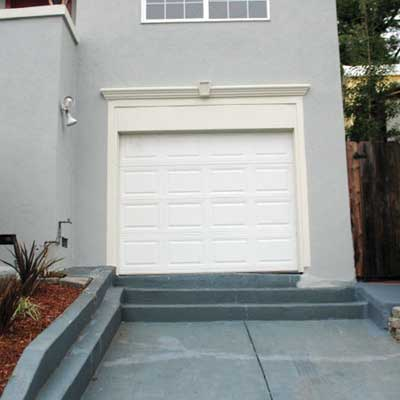 attached garage door installed at the top of three concrete steps built into the driveway