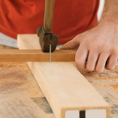 man using block of wood to pull out nail without leaving mark