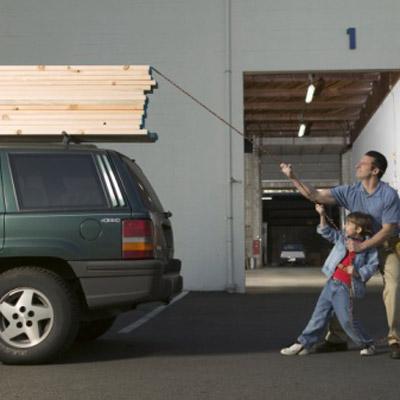 man and son lashing lumber to car