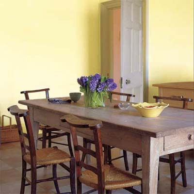 rustic limed table set in a dining room area