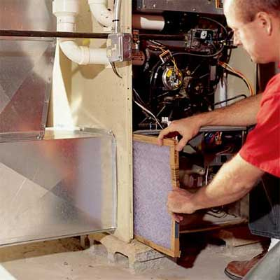 person changing a filter on a heating system