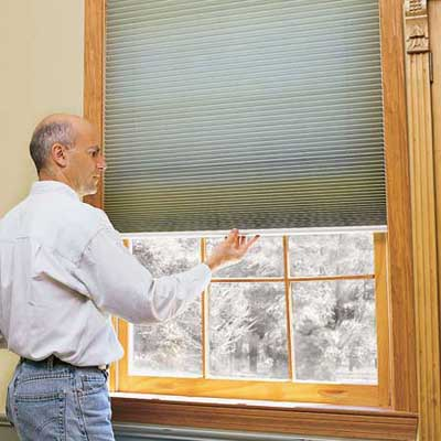 person lowering or raising some easy to clean blinds