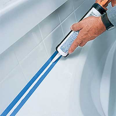 hands applying caulk between a bathtub and tile