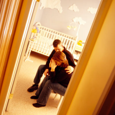 unhappy couple sitting in baby's room