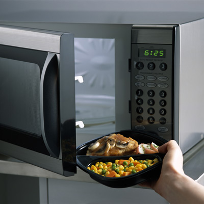 hand putting microwave dinner in oven