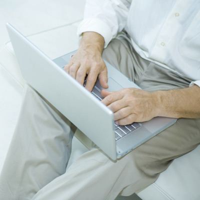 man sitting with laptop on lap