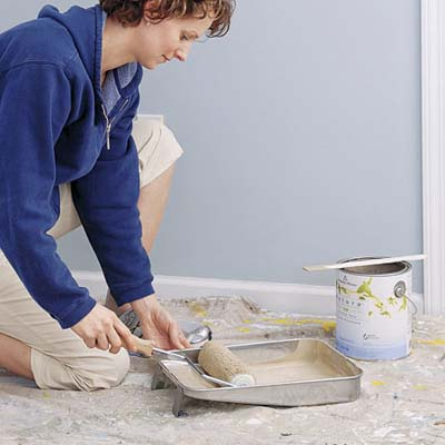 woman rolling paint in tin on drop cloth