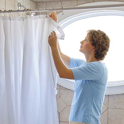 woman changing a bathroom shower curtain