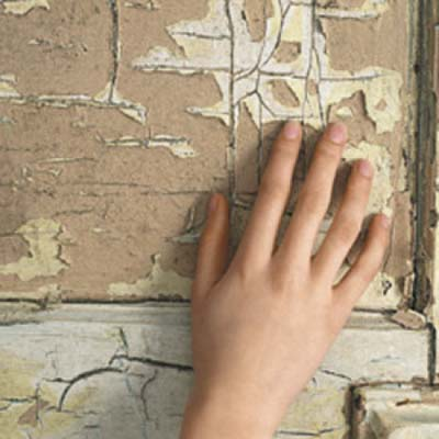 hand touching chipped painted wall
