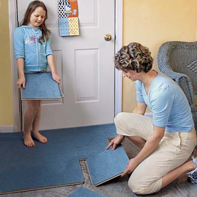 woman installing linoleum tiles to children's playroom