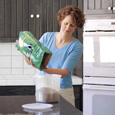 woman pouring dog food into plastic container