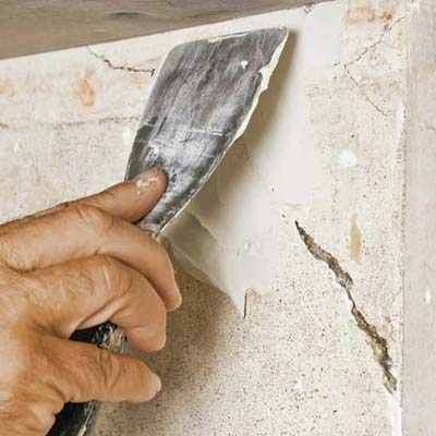 hands plastering cracked wall