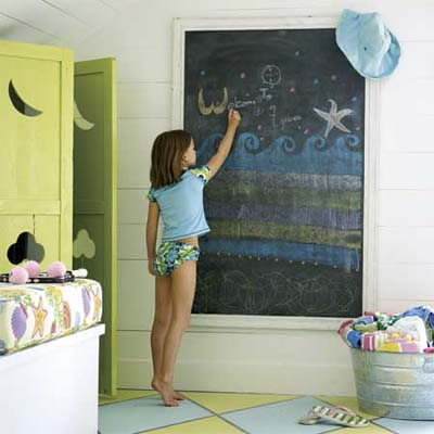 child drawing on an installed chalkboard next to shutters used as entryway doors