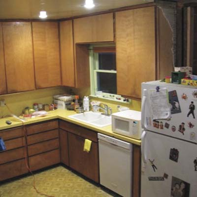 outdated kitchen with yellow laminate countertops and wooden cabinets