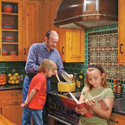 man and kids cooking in remodeled old world style kitchen with colorful tile backsplash