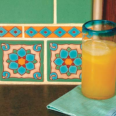 colorful hand glazed kitchen tiles and glass of orange juice