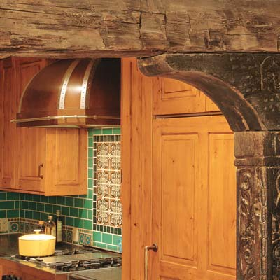 old world style kitchen with colorful tile backsplash and copper range hood