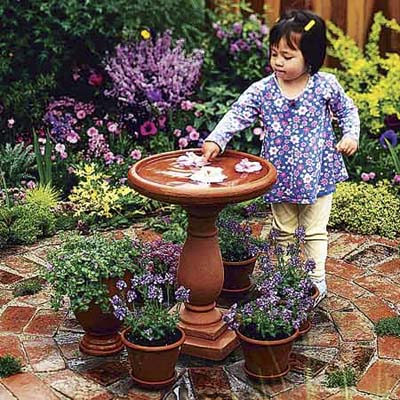 do-it-yourself, easy, affordable upgrade: little girl playing with bird bath in garden