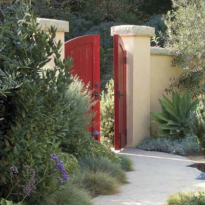 Garden entryway with bright red gate