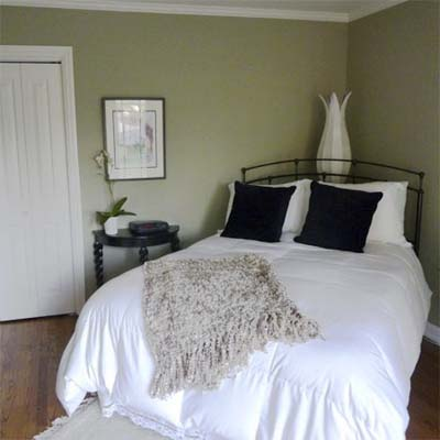updated bedroom with white bed and sage green walls