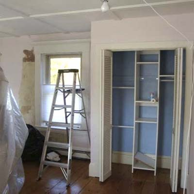 empty bedroom with open closet and ladder