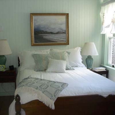 country bedroom with blue painted wooden walls and white bed