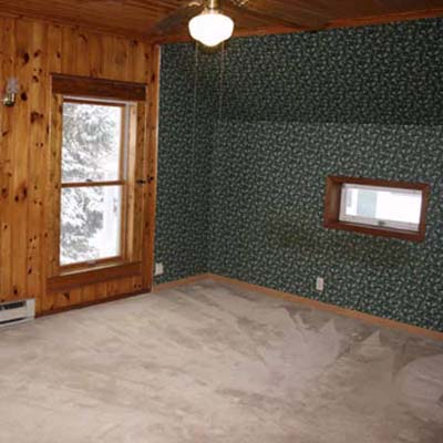 outdated bedroom with wooden walls and ceiling fan