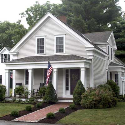 updated greek revival farmhouse with brick walkway