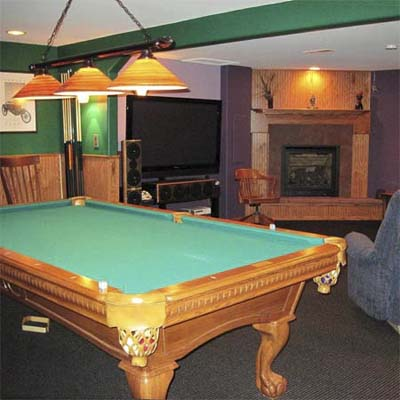 finished basement with pool table and fireplace